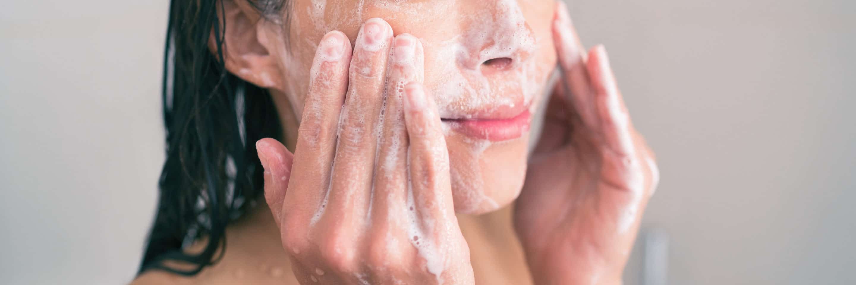 An image of a woman thoroughly cleansing her face with a white lather.